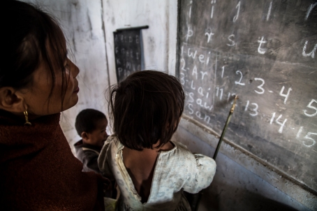 The teacher Teresa Shabong has written the Khasi numerals and alphabet on the black board. She watches with pride as her brightest student Kynja reads it aloud for the class.