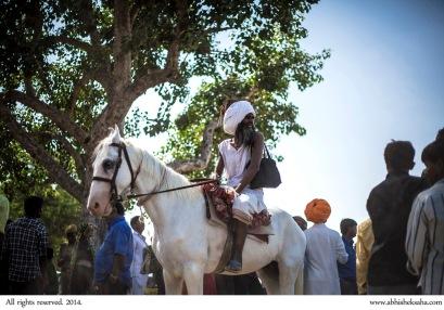 A sadhu arrives at Pushkar on horseback.