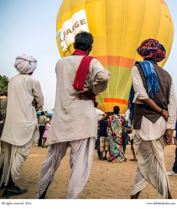 Locals observe the launch of a hot-air balloon.