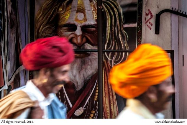 Rajasthani men walk past the portrait of a sadhu.